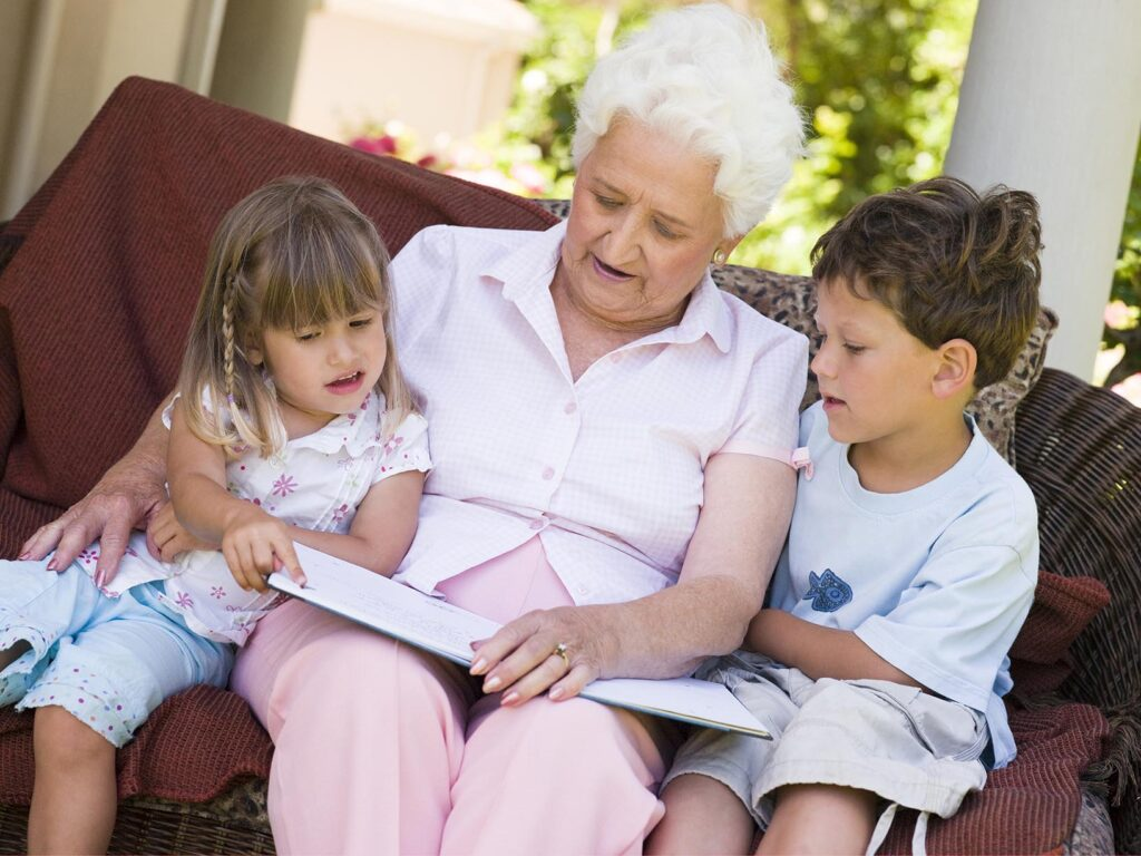 Senior woman reads to grandchildren